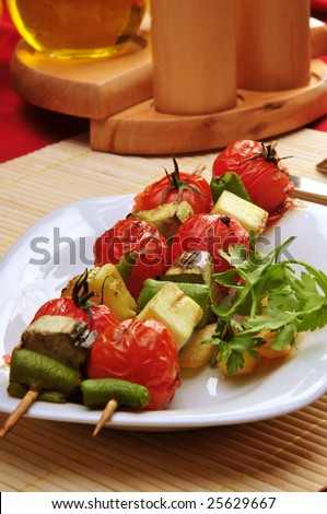 A plate full griled vegatables kabobs.
