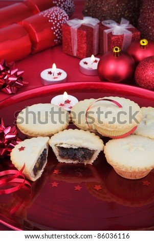 A Plate Full of Christmas Mince Pies with Red decorations in the background