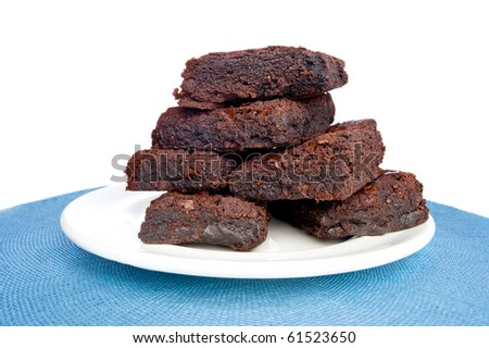 A plate full of fresh brownies on a plate with a white background