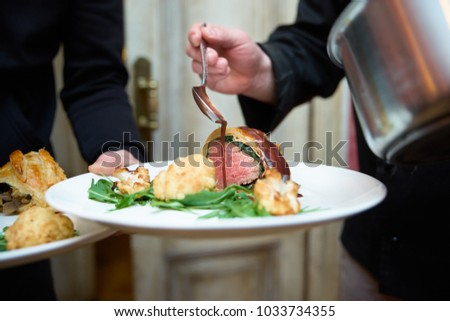 A plate in the hands of the waiter chef cooks on sauce meat. Beef tenderloin with cauliflower baked in the oven. Stockfoto ©
