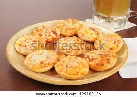 A plate of bagels with pizza toppings and a mug of beer on a bar counter