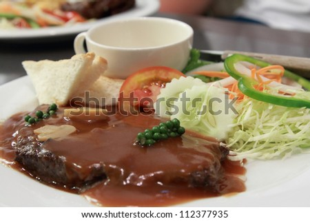 a plate of beef steak with pepper gravy