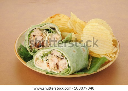 A plate of chicken caesar wraps with potato chips