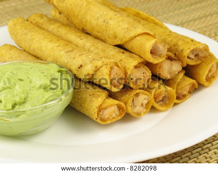 A plate of chicken taquitos with a side of guacamole.