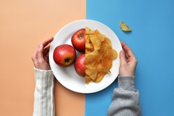 a plate of chips and red apples. A person chooses between healthy and unhealthy food