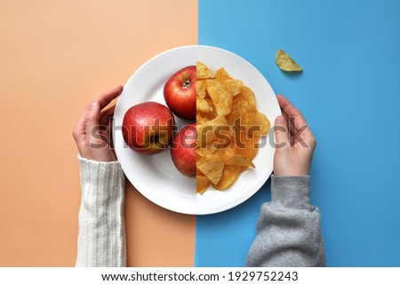 a plate of chips and red apples. A person chooses between healthy and unhealthy food Photo stock ©