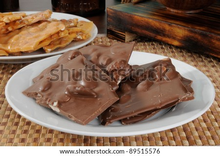 A plate of chocolate bark with almonds and of peanut brittle