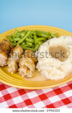 A plate of country style city chicken (which is actually pork on a stick) that has been pan browned and then baked, mashed potatoes, gravy and green beans.