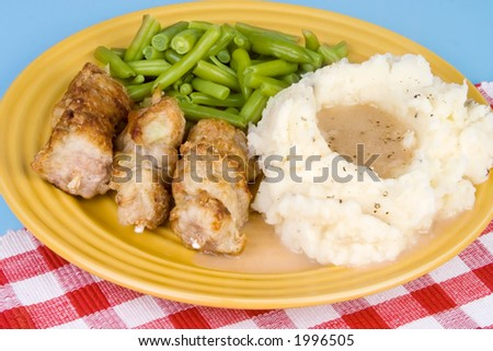 A plate of country style city chicken (which is actually pork on a stick) that has been pan browned and then baked, mashed potatoes, gravy and green beans. - stock photo