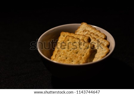 A plate of crackers on a dark background