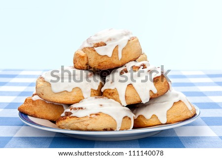 A plate of delicious cinnamon rolls coated with sugary frosting glaze.
