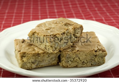 A plate of delicious pecan caramel bars, great for holidays or any time, red background with shallow depth of field, horizontal with copy space
