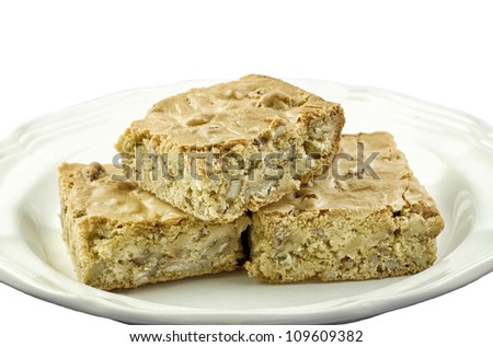 A plate of delicious pecan caramel bars on a white horizontal background with copy space