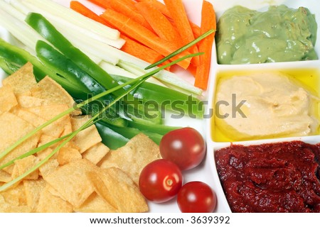 A plate of dips, with julienned carrot, capsicum and celery, tomatos and potato crisps or chips. shot for maximum depth of focus (scheimpflug effect).