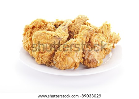 A plate of fresh, fried, crispy chicken on a white plate on a white table