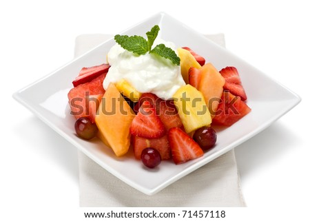 A plate of fresh fruit salad with yogurt and garnished with mint on white background.