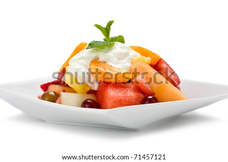 A plate of fresh fruit salad with yogurt and garnished with mint on white background. - stock photo
