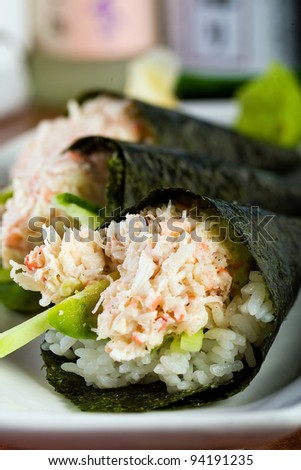 A plate of fresh hand rolled seafood sushi roll stuffed with snow crab meat and wrapped in a cone shape with seaweed.  Served at an Asian cuisine restaurant.