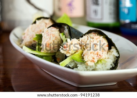 A plate of fresh hand rolled seafood sushi roll stuffed with snow crab meat and wrapped in a cone shape with seaweed.  Served at an Asian cuisine restaurant. - stock photo