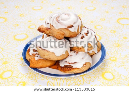 A plate of freshly baked cinnamon rolls with sugar icing dripping down the sides.
