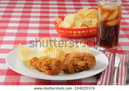 A plate of fried chicken with potato chips on a checkered tablecloth with space for your copy