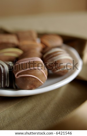 A plate of gourmet hand-dipped chocolates in a warm golden setting. Shallow focus on pink-striped chocolate.