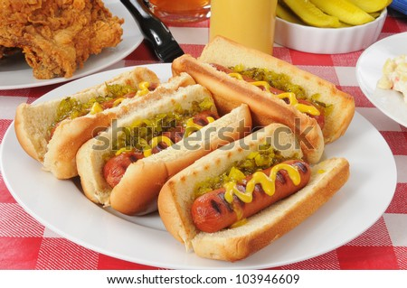 A plate of grilled hot dogs with mustard and relish on a picnic table