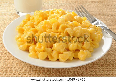 A plate of macaroni and cheese with a glass of milk