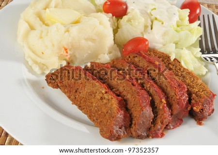 A plate of meatloaf with tomato sauce