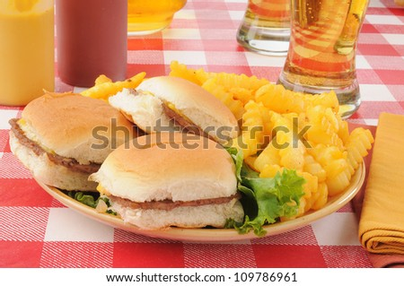 a plate of mini cheeseburgers and fries with a glass of beer