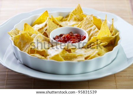 a plate of nachos with salsa and tortilla chips