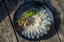 A plate of pearly white Fugu Pufferfish sashimi with chopped chives at Karatocho fish market in Shimomoseki Yamaguchi Prefecture Japan.