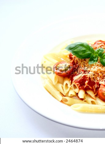 A plate of penne pasta tubes with rich tomato sauce and sprinkling of grated cheese, garnish with cherry tomatoes and sprig of basil - stock photo