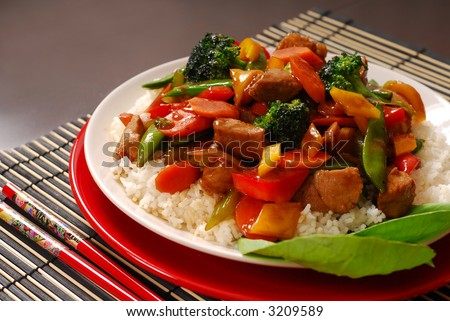 A plate of pork stir fry with vegetables