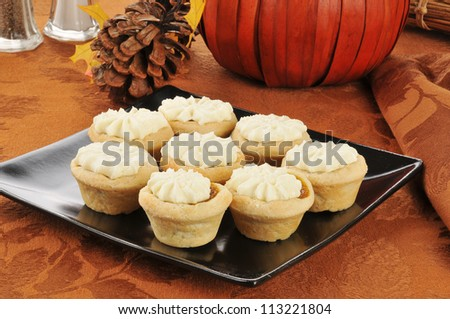 A plate of pumpkin tarts on a festive Halloween or Thanksgiving table setting with cream cheese icing