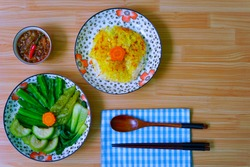 A plate of Scorched Rice served with caramelized fish sauce, and many kinds of boiled vegetables and beans. Vietnamese dish. (Vietnamese name : Com chay mam kho quet). Flat lay.