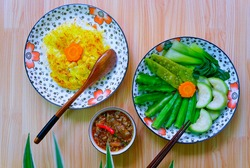 A plate of Scorched Rice served with caramelized fish sauce, and many kinds of boiled vegetables and beans. Vietnamese dish. (Vietnamese name : Com chay mam kho quet). Top view, flat lay.