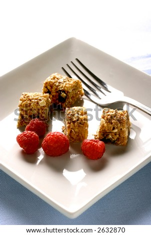 A plate of sliced up muesli bar with a few scattered raspberries. Concept of quick and nutritious food.