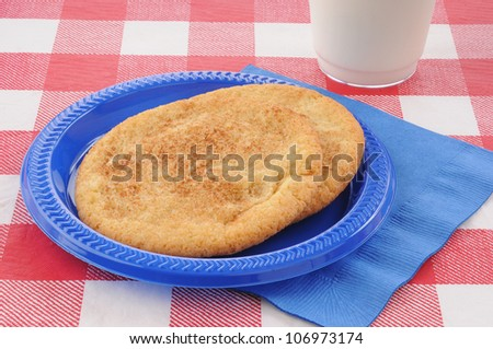 A plate of snickerdoodle cookies on a picnic table with milk