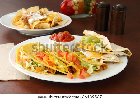 A plate of soft and crunch tacos with salsa and nachos in the background