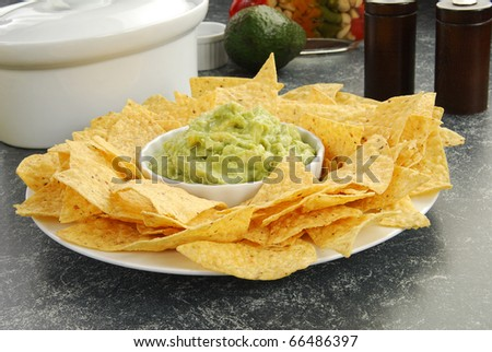 A plate of tortilla chips with organic guacamole