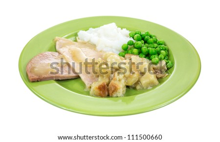 A plate of turkey slices stuffing and vegetables.