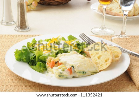A plate of vegetable lasagna with salad and wine