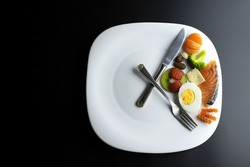 a plate simulating a clock with the hands of a fork and a knife showing food, concept of intermittent fasting
