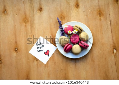 A plate with colorful macaroons and a note with get well soon text on rustic wooden table  #1016340448