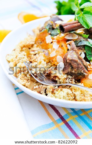 A plate with delicious looking couscous with lamb meat, apricots, almonds, raisins, dates, cinnamon and mint. Vertical shot with better view of the meat.