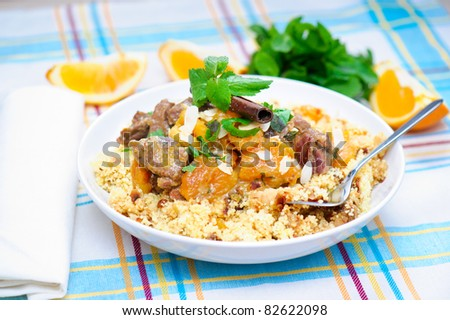 A plate with delicious looking couscous with lamb meat, apricots, almonds, raisins, dates, cinnamon and mint. I used some mint leaves, a white napkin and orange slices in the background.