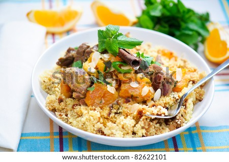 A plate with delicious looking couscous with lamb meat, apricots, almonds, raisins, dates, cinnamon and mint. I used some mint leaves and orange slices in the background.