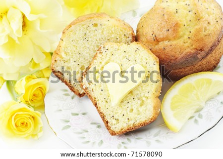 A plate with fresh baked lemon poppy seed muffins with heart shaped butter on muffin, concept - stock photo