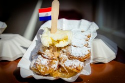 A plate with fresh baked Poffertjes with banana. Poffertjes are a traditional Dutch batter treat